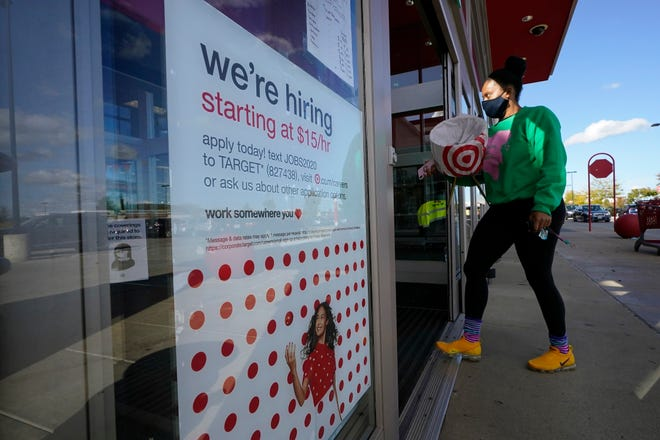 FILE - In this Sept. 30, 2020, file photo, a passerby walks past a hiring sign while entering a Target store in Westwood, Mass. The number of Americans applying for unemployment benefits edged higher last week to 745,000, a sign that many employers continue to cut jobs despite a drop in confirmed viral infections and evidence that the overall economy is improving.   (AP Photo/Steven Senne, File)