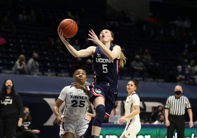 UConn guard Paige Bueckers (5) shoots ahead of Xavier guard Carrie Gross (25) during the first half of an NCAA college basketball game Saturday, Feb. 20, 2021, in Cincinnati.