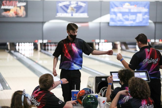 Seaman's Zander White gets congratulations from his teammates after getting a strike during Thursday's Class 5-1A State Bowling Tournament at Northrock Lanes.