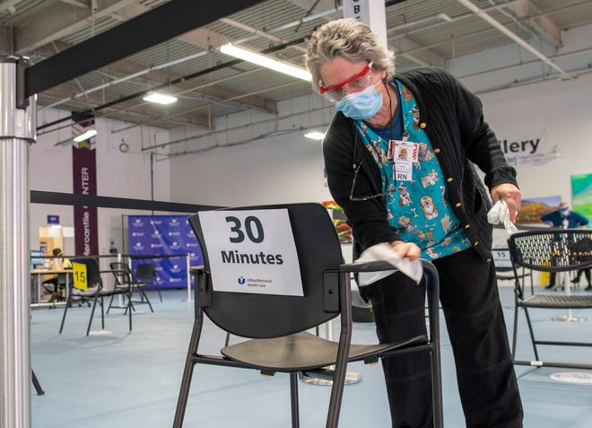 Terri Pecevich, RN, sanitizes chairs used to observe people after they receive a COVID-19 vaccination Friday at the Mercantile Center vaccination site run by UMass Memorial Medical Center.