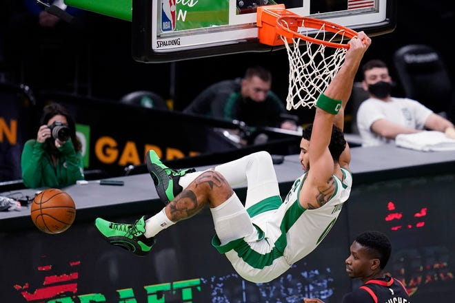 Boston Celtics forward Jayson Tatum (0) hangs on the rim after dunking during the first half of Thursday's game.