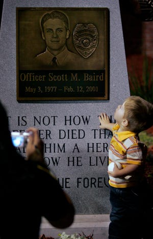 Logan Baird, the then-2-year-old nephew of the late Officer Scott Baird, looks up at a plaque on the side of a flagpole and granite monument before getting his picture taken by Officer Tracy Plank after the dedication ceremony of the Scott Baird Baseball Complex at Gainesville High School in February 2007. Baird was killed Feb. 12, 2001 after responding to a late night call to remove a batting cage from the middle of the street when a car barreled into the cage as he was moving it.