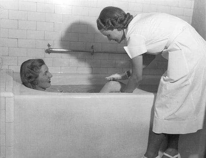 A bath attendant bathes a patron in one of the baths in 1938.