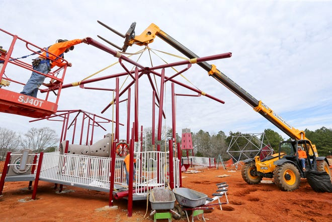 A work crew from Struthers Recreation raises the frame that will hold a canopy above one of the pieces of playground equipment in the All-Inclusive Playground in Sokol Park Friday, March 5, 2021. [Staff Photo/Gary Cosby Jr.]