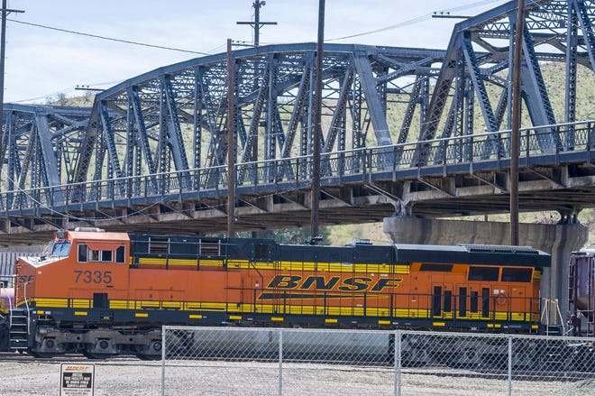 A BNSF train passes under the First Avenue Bridge in Barstow in 2019.
