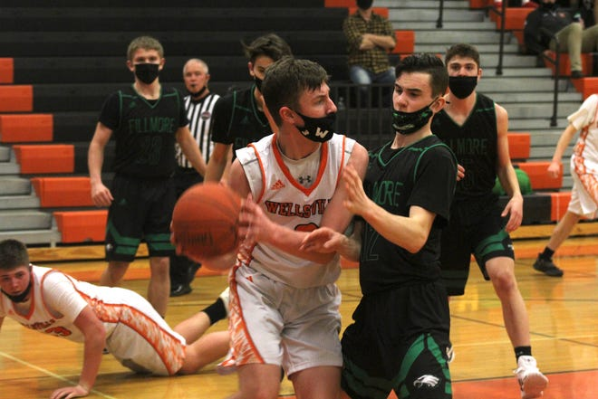 Wellsville's Alex Perkins operates on the baseline as Fillmore's Carter Sisson (12) defends Thursday night.