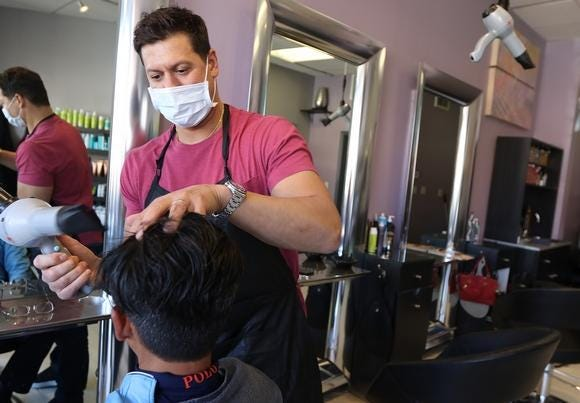 Louis Volpicelli, co-owner of Stephanie Louis Salon in Lexington center, wears a mask at the customer's request while styling his hair Wednesday, March 18, 2020.