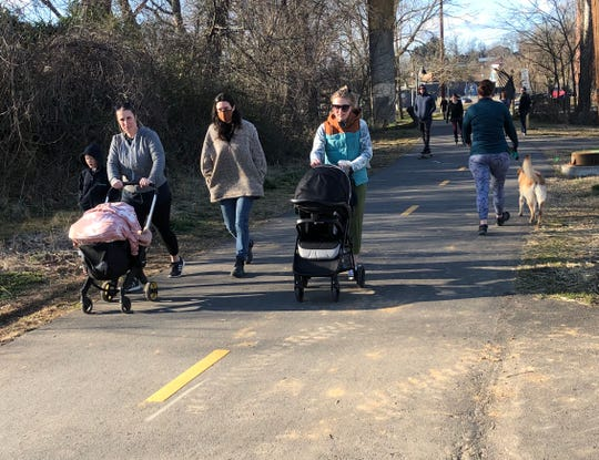 A group of moms with baby strollers enjoy the River Arts District Greenway on Thursday, March 4, along with dog walkers and other users. The recreational path along the French Broad River is now named the Wilma Dykeman Greenway.