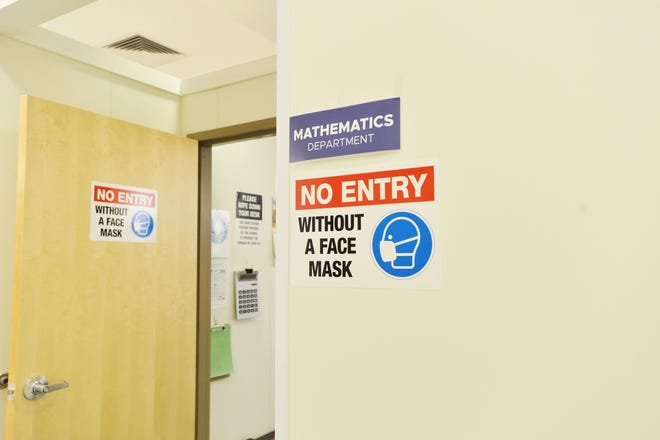 A sign outside a math class at Downtown Burlington High School reminds students to wear a face mask to prevent the spread of COVID-19. Pictured March 4, 2021. The highs school resumed classes in the former Macy's department store building.