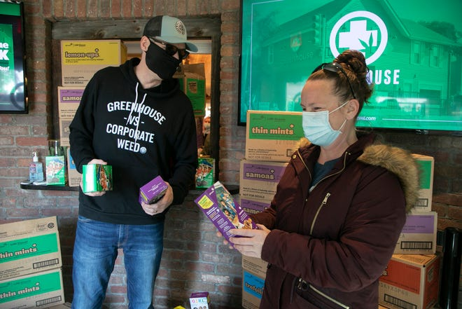 Greenhouse of Walled Lake owner Jerry Millen, left, buys 301 boxes of Girl Scout cookies from Jennifer Slayden, 39, of Oakland County on Friday, Mar. 5, 2021, after Slayden, a mother of two Girl Scouts, was disappointed about her daughter's lack of opportunity to sell more Girl Scout Cookies after the Girl Scouts of the USA are forbidding the Oakland County Girls Scouts to sell their cookies in front of the Marijuana dispensary Greenhouse of Walled Lake after they had gangbuster sales last weekend.