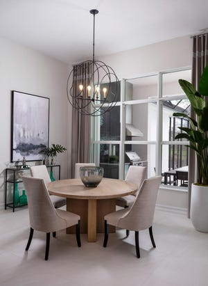 The dining area in the new Covington III model is set beside a wall of windows overlooking the lanai and pool.