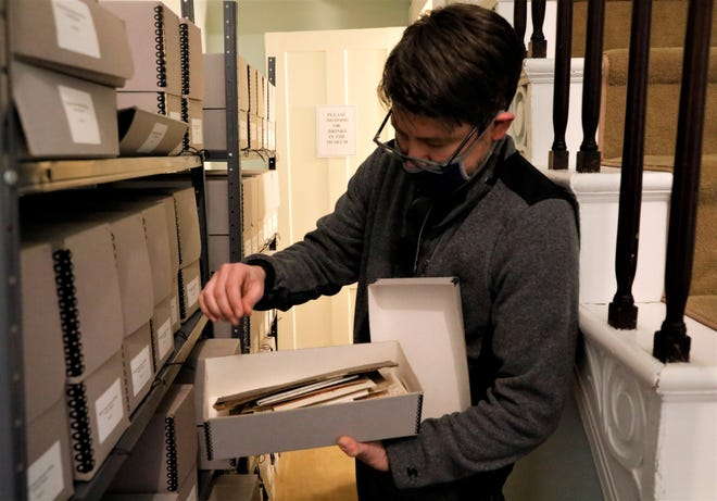 Jason Crabill, executive director of the Decorative Arts Center of Ohio, looks through a box containing receipts, contracts and bills of sale Thursday, March 4. The box is part of an archival collection of documents and photos from the Rising, Peters and Reece families, dating from the late 1800s to the 1990s.