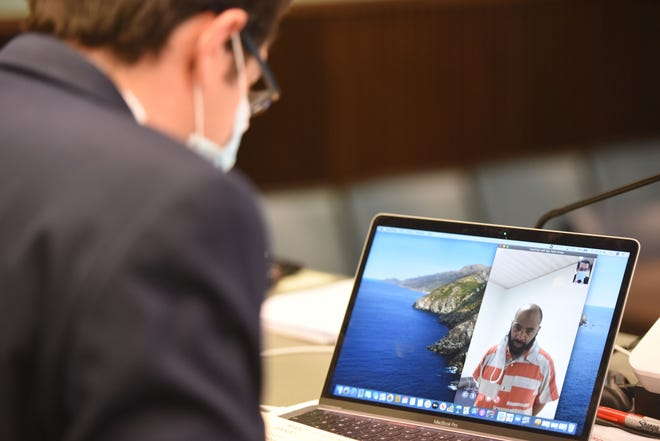Magistrate John D. McCollister uses his computer to video conference with John Mack on Friday morning during his arraignment for kidnapping.