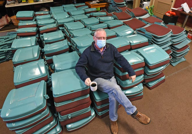 Doug Wertz sits among more than 300 chairs recently purchased on eBay.
