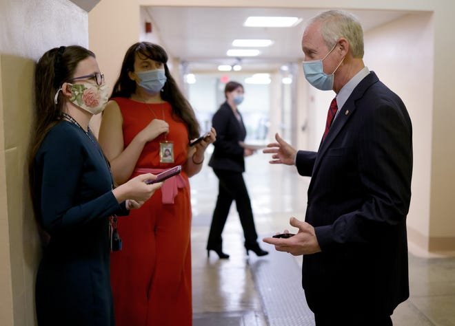Sen. Ron Johnson of Wisconsin talks with reporters while walking to the U.S. Senate chamber for a vote in Washington, D.C., on Friday.