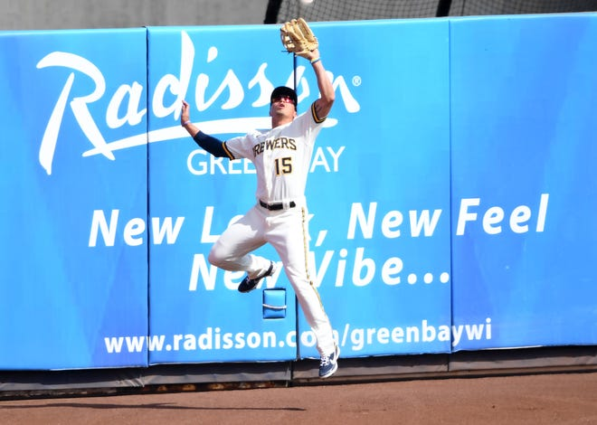 Tyrone Taylor of the Brewers makes a leaping catch near the wall in center field to take a hit away from Cleveland's Andres Gimenez in the second inning.