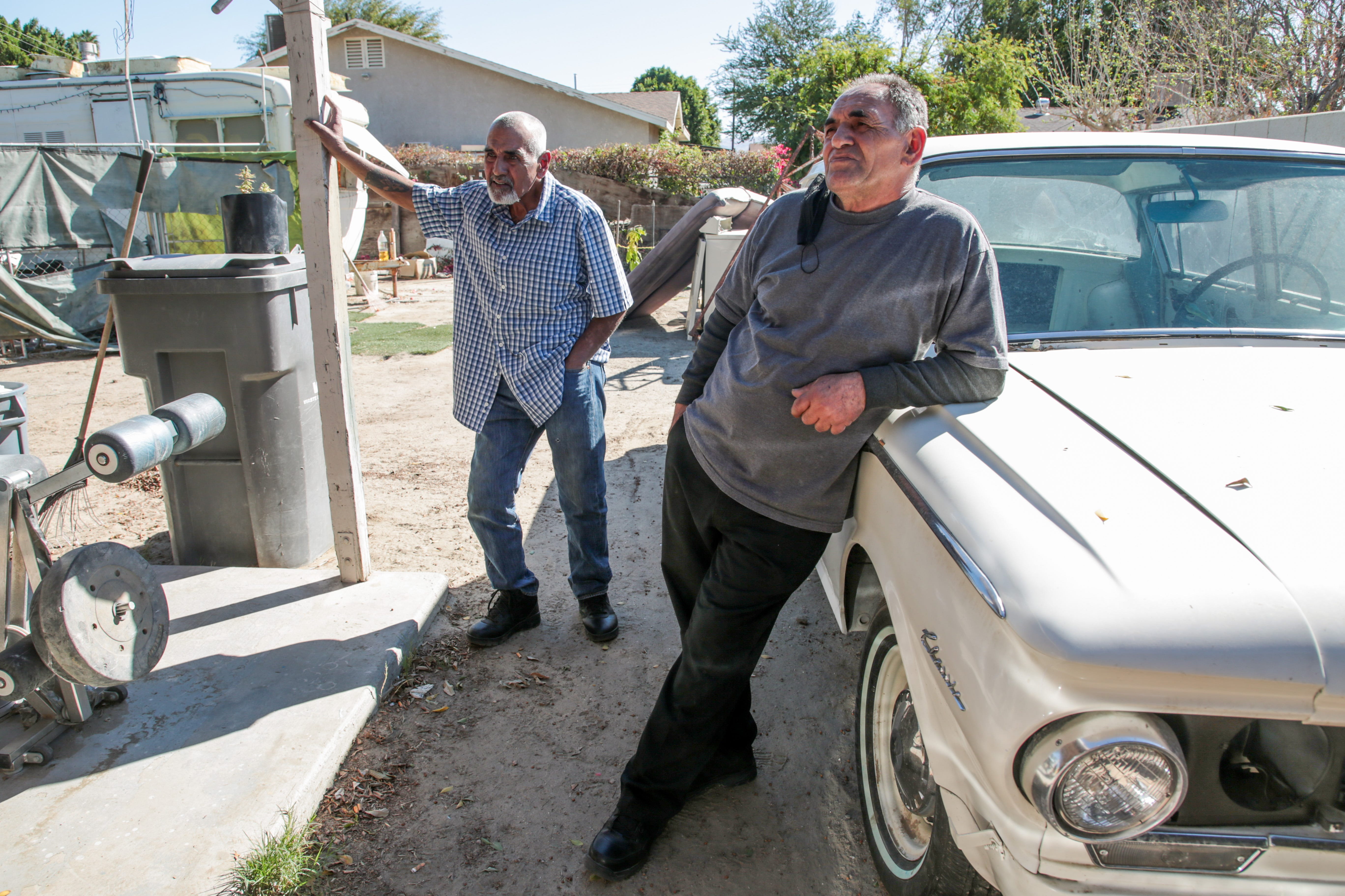 Luis Carlos Morin Sr., left, and brother Hector Morin, right, stand in their backyard in Coachella Feb. 25, 2021. Former Riverside County Sheriff's Deputy Oscar Rodriguez has been charged in the 2014 fatal shooting of Luis Morin Jr., Carlos' son.