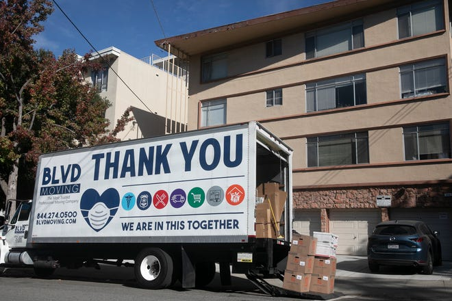 A moving truck with COVID-19 aware messaging outside of an apartment building in Oakland on Nov. 7, 2020.