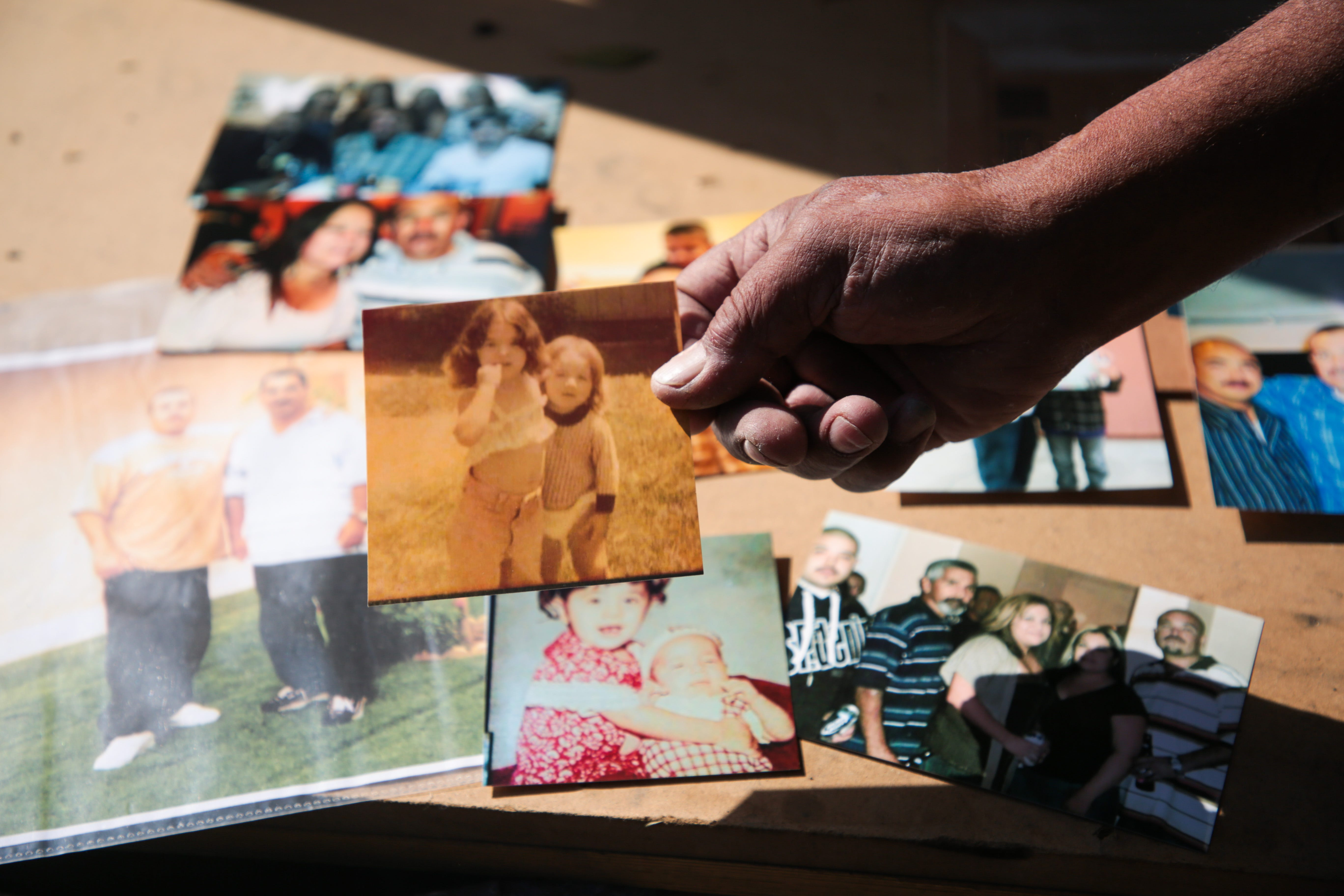 Luis Carlos Morin Sr. goes through photos of his son, Luis Carlos Morin Jr., right, at his home in Coachella on Feb. 25, 2021. Former Riverside County Sheriff's Deputy Oscar Rodriguez is being prosecuted for fatally shooting Luis Morin Jr. in 2014.