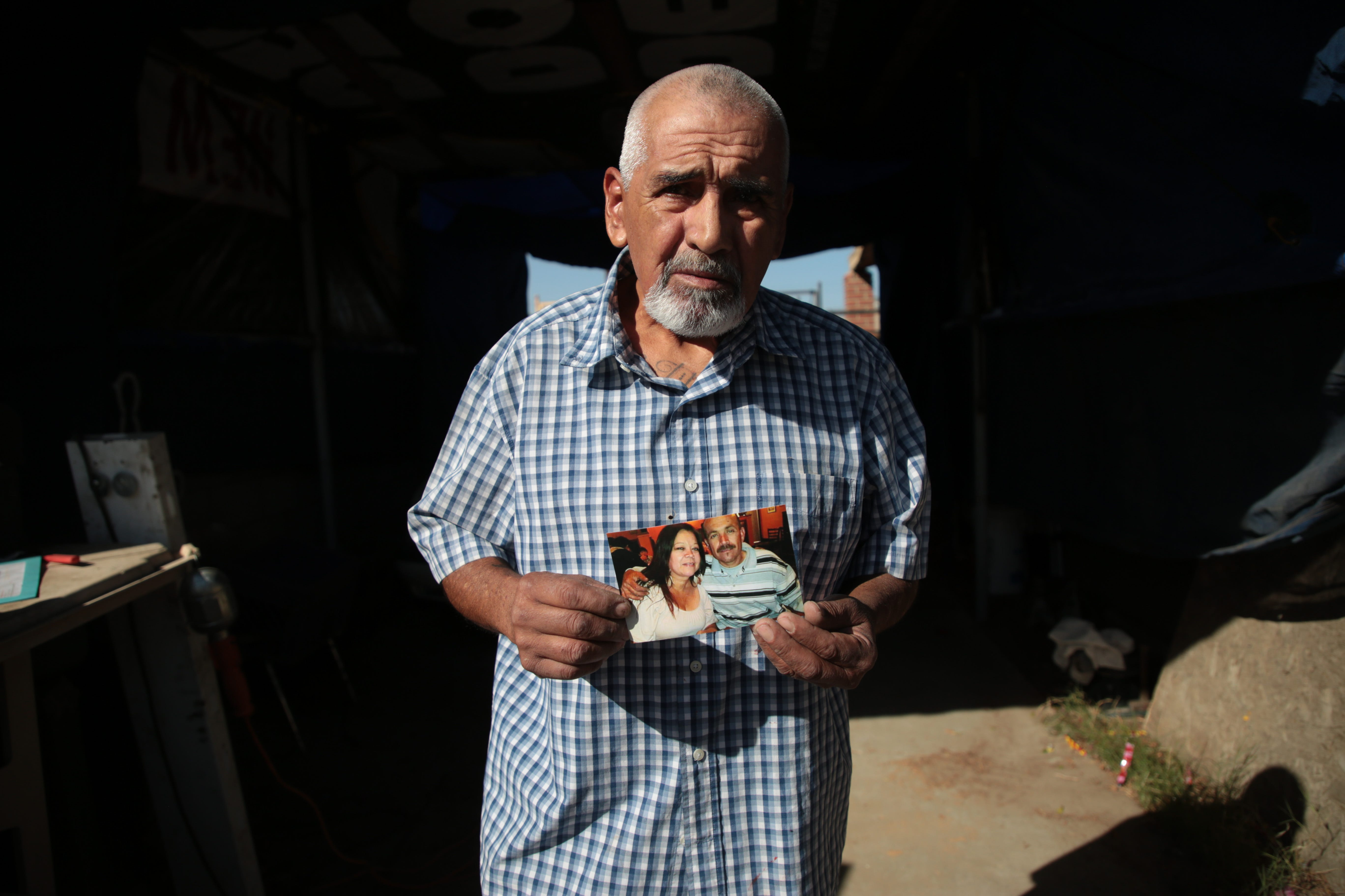 Luis Carlos Morin Sr. holds a photo of his son, Luis Carlos Morin Jr., right, at his home in Coachella  on Feb. 25, 2021. Former Riverside County Sheriff's deputy Oscar Rodriguez is being prosecuted for fatally shooting Luis Morin Jr. in 2014.