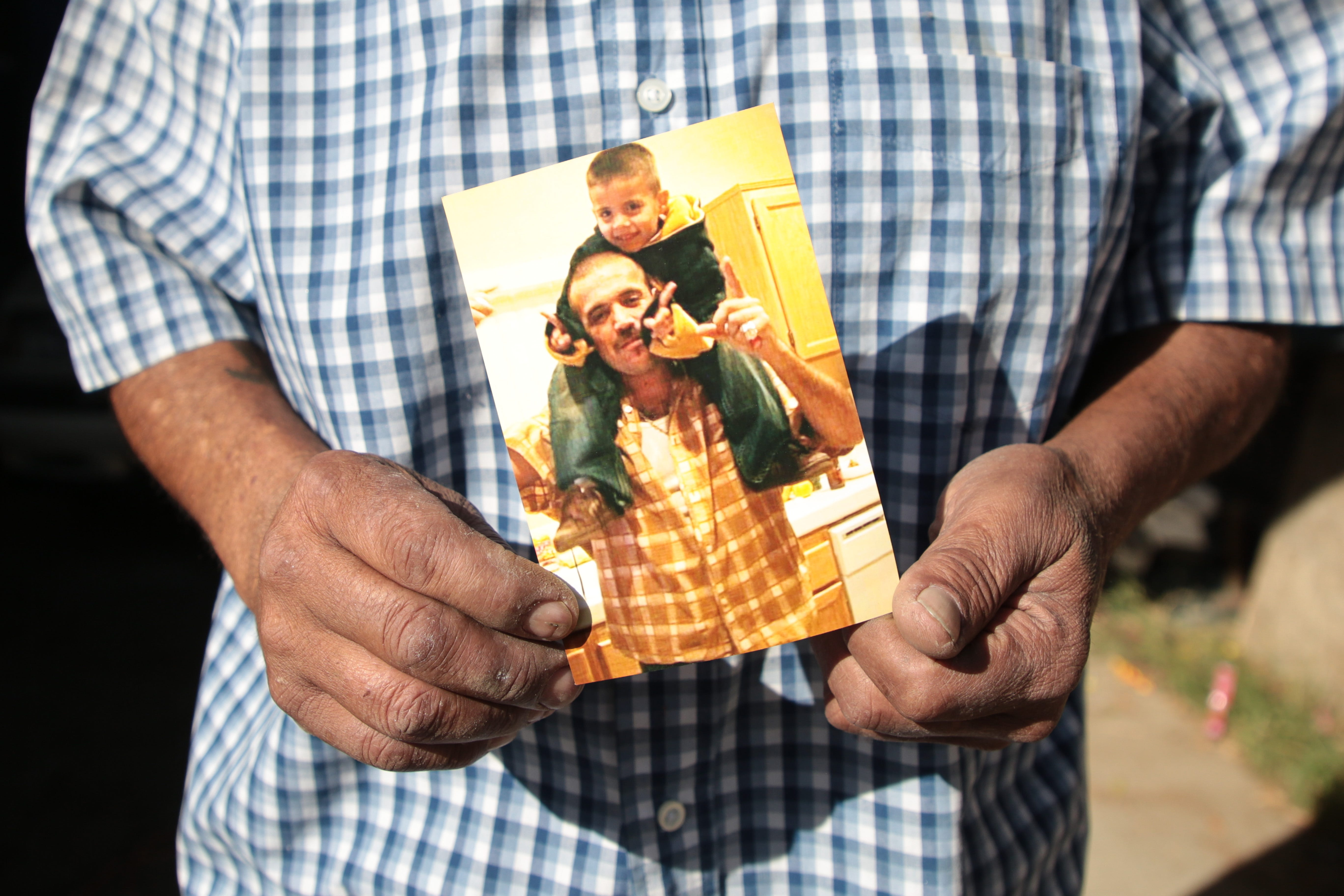 Luis Carlos Morin Sr. holds a photo of his son, Luis Carlos Morin Jr., and his grandson at his home in Coachella, on Feb. 25, 2021. Former Riverside County Sheriff's Deputy Oscar Rodriguez is accused of fatally shooting Luis Morin Jr. in 2014.