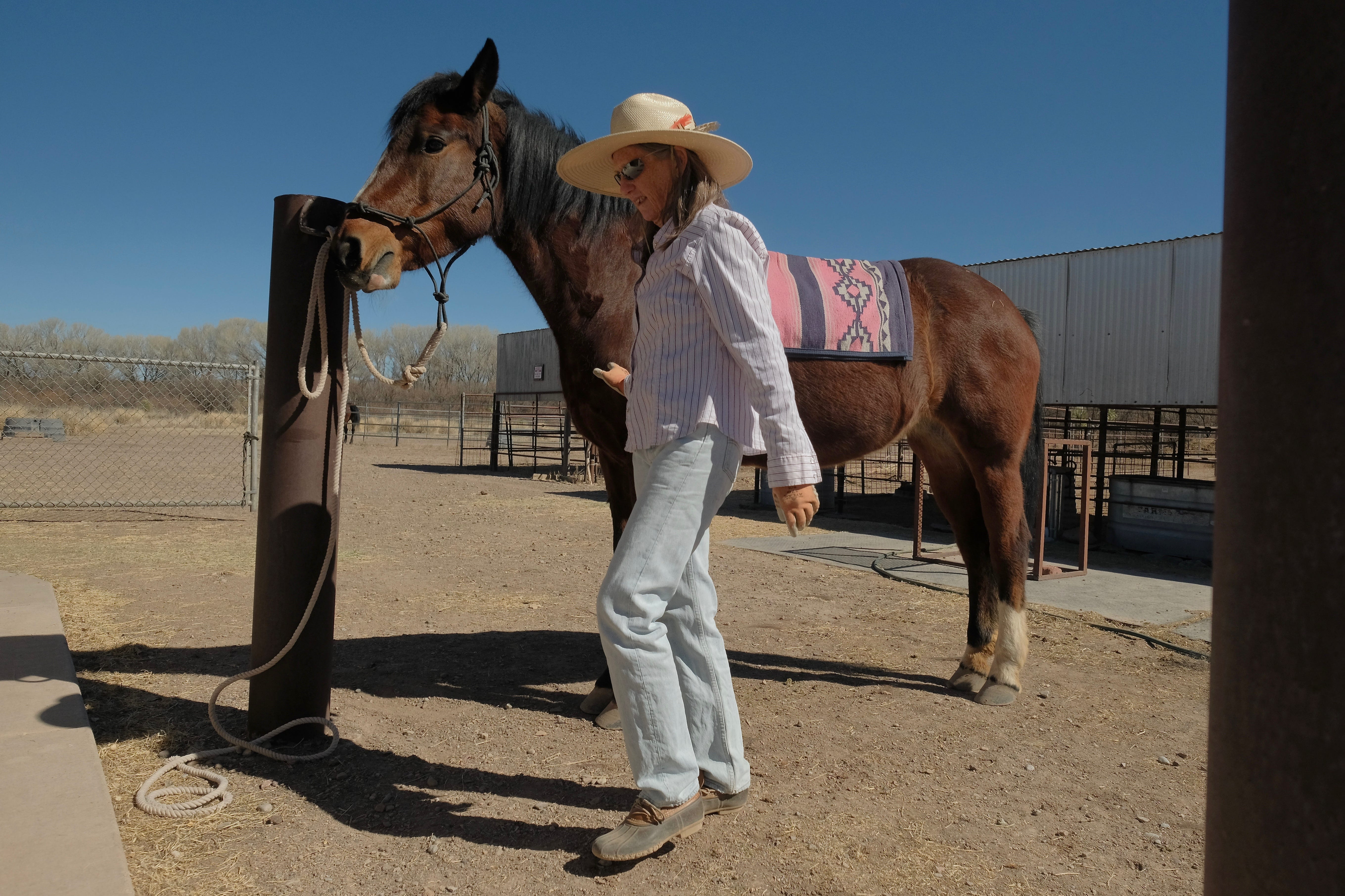 Sandy Anderson and one of two adopted wild horses that she trained herself at her property about 12 miles from the border on Feb. 5, 2021.