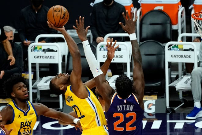 Golden State Warriors forward Andrew Wiggins (22) drives against Phoenix Suns center Deandre Ayton (22) during the first half of an NBA basketball game, Thursday, March 4, 2021, in Phoenix. (AP Photo/Rick Scuteri).