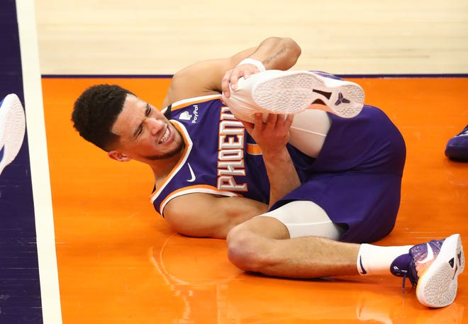 Mar 4, 2021; Phoenix, Arizona, USA; Phoenix Suns guard Devin Booker reacts after suffering an injury against the Golden State Warriors in the first half at Phoenix Suns Arena. Mandatory Credit: Mark J. Rebilas-USA TODAY Sports