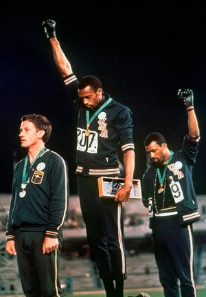 Tommie Smith, middle, and John Carlos, right, extend gloved hands skyward in a Black Power salute at the 1968 Summer Olympics in Mexico City.