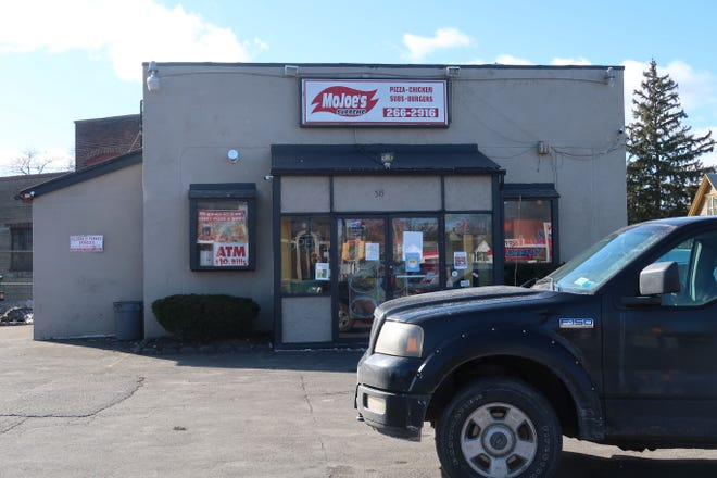 A woman holding her 3-year-old daughter was confronted by two Rochester police officers outside MoJoe's Take Out, 515 Portland Ave., on Feb. 22.