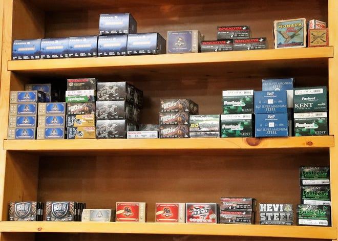Boxes of ammunition sit for sale on a shelf inside a gun shop.