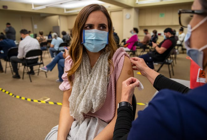 Angela Fuidge, right, a registered nurse at Salinas Valley Memorial Healthcare System, puts a bandaid on Meredith Jones, a 1st grade teacher at Mission Park Elementary School, after she received her first dose of the Pfizer COVID-19 vaccine in Salinas, Calif., on Thursday, March 4, 2021.