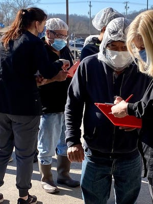 Workers at a Tyson chicken plant in Noel, Missouri wait to receive a vaccine for COVID-19.