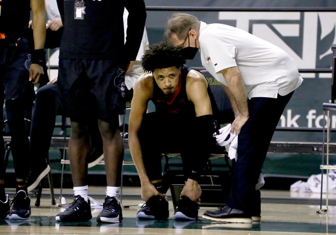 Oklahoma State guard Cade Cunningham holds his ankle after being injured during the Cowboys' loss to Baylor.