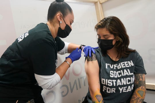 Denise Padilla, right, an instructor at the culinary school at Eva's Village, is vaccinated in Secacus, N.J., Sunday, Feb. 28, 2021.