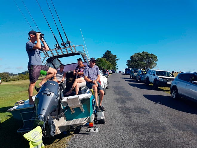 John Fitzgerald, left, scans the horizon from high ground for any sign of a tsunami on Friday near Waitangi, New Zealand.
