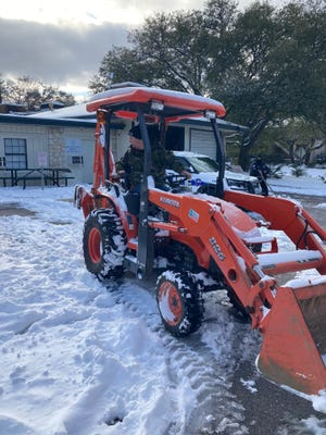 Rollingwood Police Chief Jason Brady drives a tractor as the city was hit by a snow and ice storm in February.