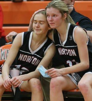 Norton's Bailey Shutsa, left, is comforted by Bailey Acord late in the fourth quarter of the Panthers' 47-35 loss to Napoleon in a Division II regional final in Mansfield. [Mike Cardew/Beacon Journal]