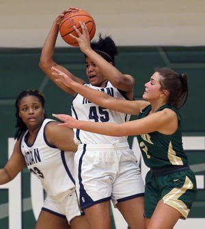 Archbishop Hoban junior forward Lanae Riley hauls down a rebound during the Knights' Division II regional final win over GlenOak. [Jeff Lange/Beacon Journal]