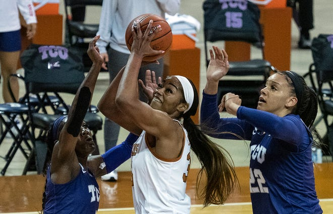 Texas forward Charli Collier splits TCU defenders Aahliyah Jackson and Kayla Mokwuah while going up for a shot in the Longhorns' 71-54 win in Austin on Jan. 20.