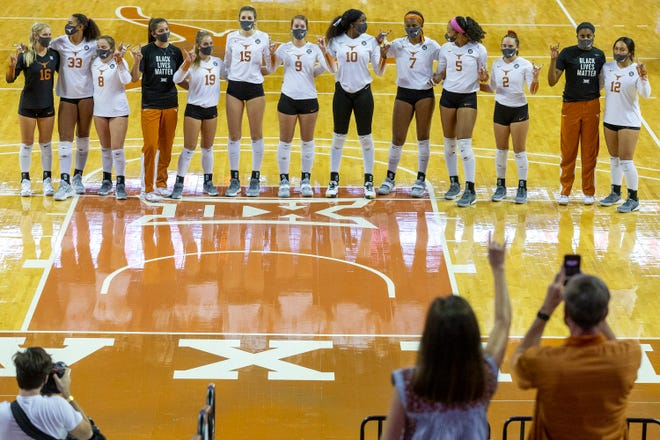 """The Texas volleyball team stands together during the playing of """"The Eyes of Texas"""" after a victory over Texas Tech at the Erwin Center in October."""