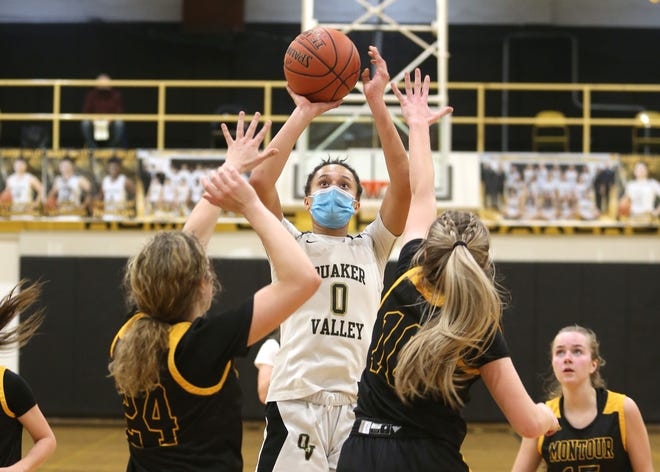 Quaker Valley's Corinne Washington (0) attempts a three point shot while being guarded by Montour's Olivia Lyscik (24) and Olivia Persinger (10) during the first half of the WPIAL 4A Playoffs Friday night at Quaker Valley High School.