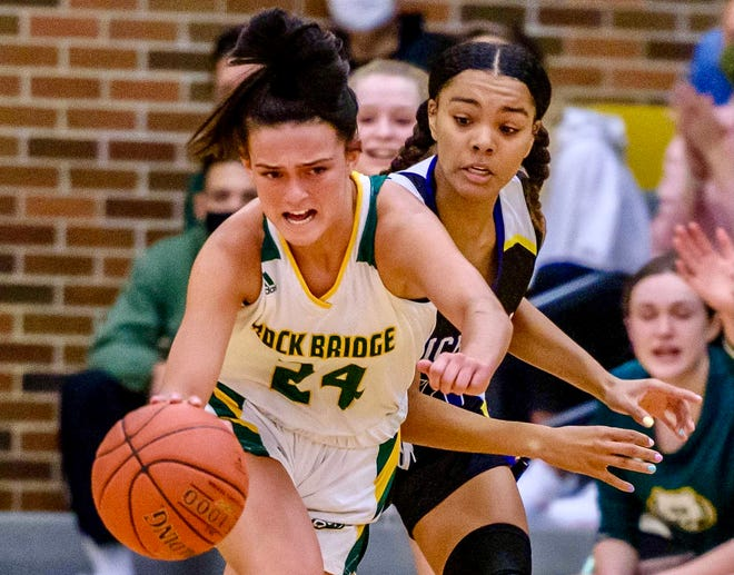 Rock Bridge's Haylie Sims (24) drives past Hickman's Kalia Naylor (13) during the Class 6 District 8 championship Friday night at Rock Bridge High School.