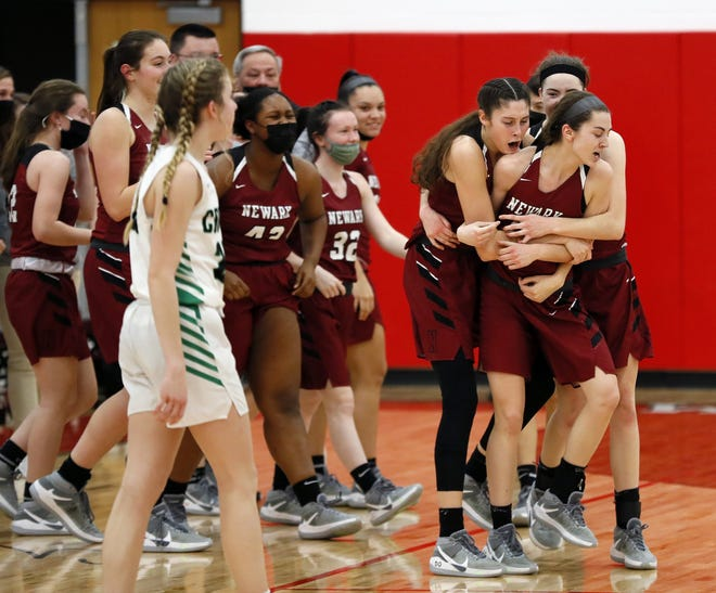 Newark's Gwen Stare, front right, is mobbed by her teammates after scoring the winning basket in a regional final victory over Dublin Coffman, sending the Wildcats to the state tournament.