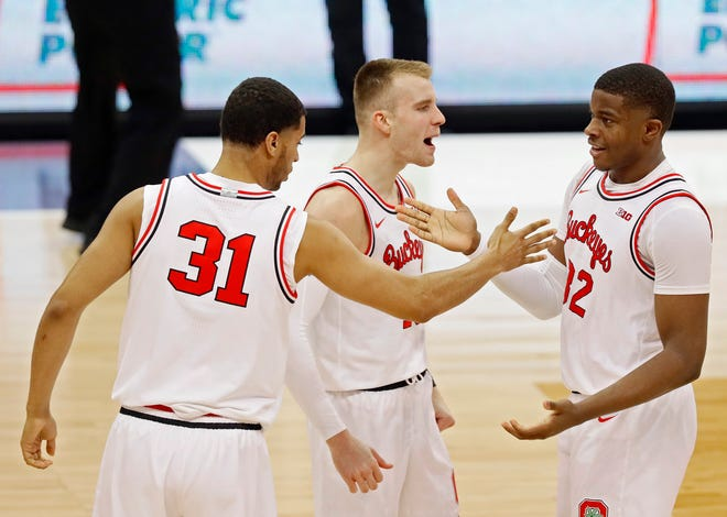 Ohio State Buckeyes forward E.J. Liddell (32) celebrates his three pointer against forward Justin Ahrens (10) and forward Seth Towns (31) against Illinois Fighting Illini during the second half of their game at Value City Arena in Columbus, Ohio on March 6, 2021.