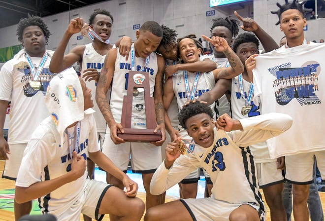 Wildwood's celebrates with the hardware Friday after winning the FHSAA Class 1A state championship against Milton Central at the RP Funding Center in Lakeland. [PAUL RYAN / CORRESPONDENT]