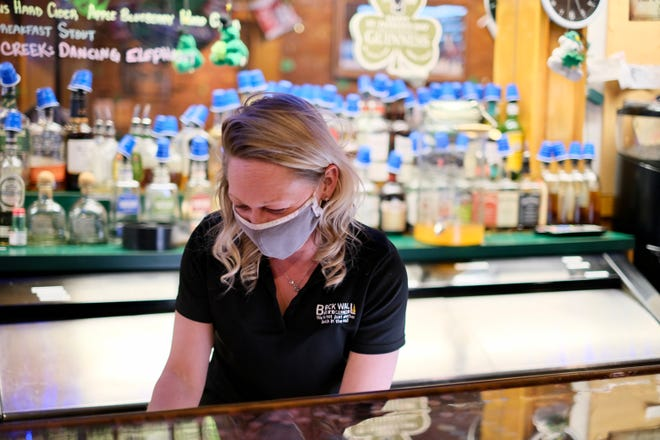 Jodi Kohlruss, manager of The Brick Wall Pub & Grill in Adrian, prepares the bar at closing time Friday.