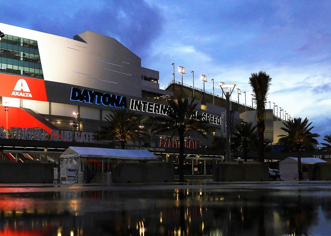 Daytona International Speedway's main sign is backed by blue light to mark a year of dealing with COVID.
