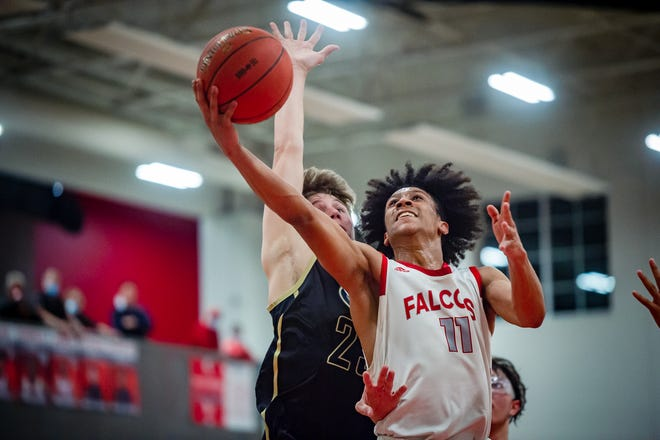 Van Horn senior guard Jaden Monday (11) takes the ball to the hoop against William Chrisman defender Dayne Herl in Friday's Class 5 District 14 championship game. Monday scored 25 points to help lead the Falcons to a 61-52 win over the Bears and their first district title since 1995.