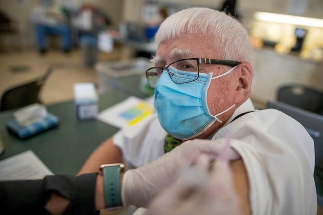 Retired doctor Robert Hickerson watches as OSF St. Mary Medical Center RN Jeanette Shipp administers the Moderna COVID-19 injection at the hospital's vaccine clinic on Mar. 5, 2021.